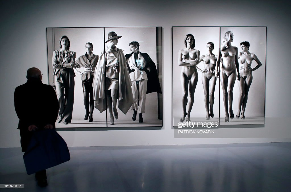 A man looks at pictures untitled 'Sie Kommen' (Naked and Dressed)) by Helmut Newton as he visits the exhibition 'Mannequin, le Corps de la Mode' at the cite de la mode fashion museum in Paris, on February 14, 2013.