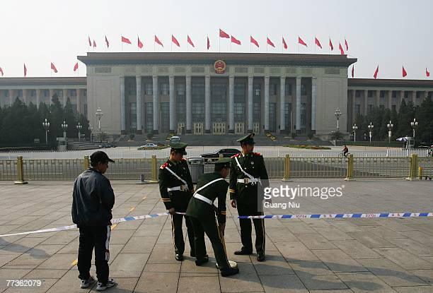A man looks at policemen making more space in front of the Great Hall of the People on the third day of the fiveyearly Chinese Communist Party...