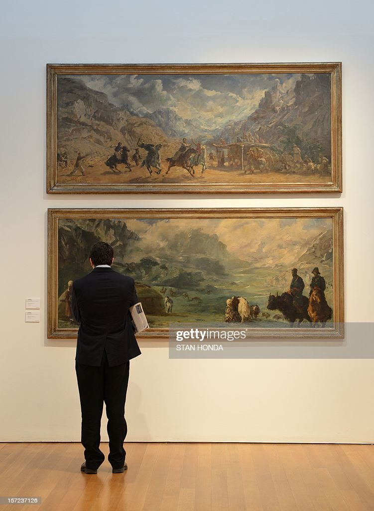 A man looks at 'Polo game at Misgar' (top), estimate of USD $150,000 to $200,000 and 'Kirghiz Encampment on the 'Roof of the World'' (bottom), estimate of USD $150,000 to $200,000, both by Alexandre Iacovleff on display in 'The National Geographic Collection: The Art of Exploration' at Christie's November 30, 2012 in New York. Fine art from the archives of the National Geographic Society will be auctioned on December 6. AFP PHOTO/Stan HONDA