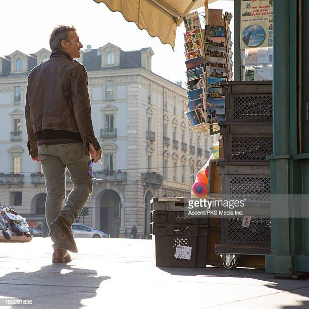 Man looks at postcard rack in piazza, city centre