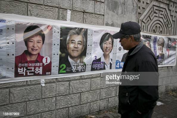 A man looks at posters of South Korean presidential candidates Park Geun Hye from the ruling New Frontier Party from left Moon Jae In from the main...