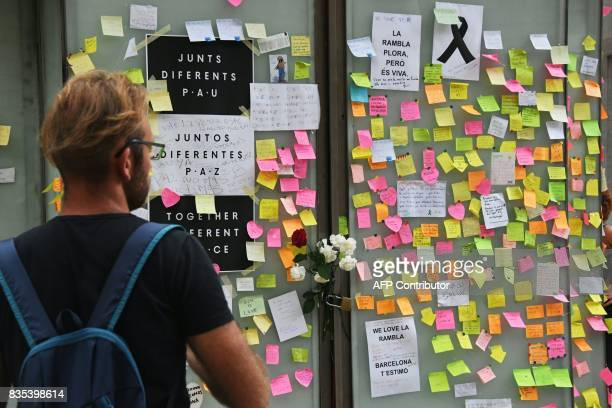 A man looks at postit notes with messages against the attacks and in tribute to the victims of the Barcelona attack on a kiosk on Las Ramblas...