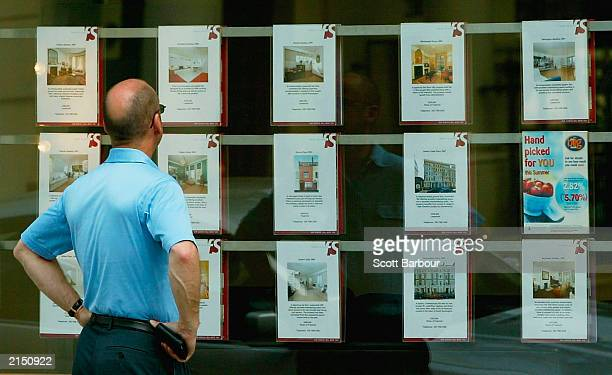 A man looks at properties for sale in an estate agents window July 10 2003 in London England House price growth slowed in June but the property...