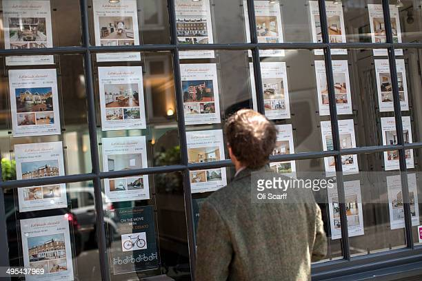 A man looks at property details displayed in the window of an estate agent in Camden on June 3 2014 in London England Figures from the Nationwide the...