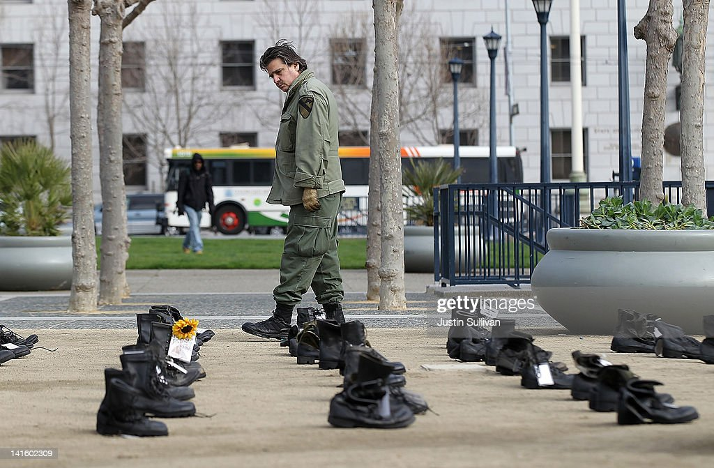 A man looks at rows of combat boots that are part of the 'Eyes Wide Open' exhibit in front of San Francisco City Hall on March 19, 2012 in San Francisco, California. The Eyes Wide Open exhibition includes a pair of boots for every one of the 481 California servicemen and women who died in the Iraq war.