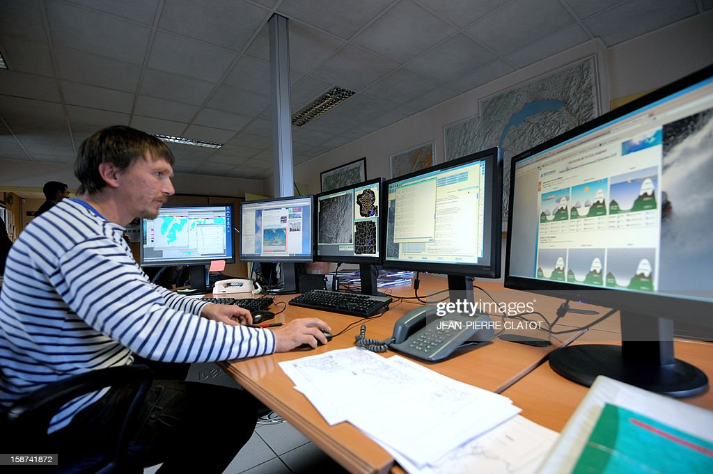 A man looks at screens at the weather station of Chamonix, French Alps, on December 26, 2012, to prepare forecasts and to evaluate the risk of avalanches. AFP PHOTO / JEAN-PIERRE CLATOT