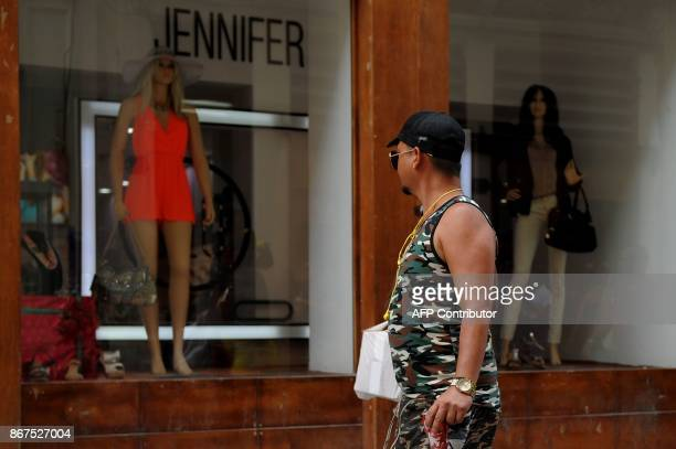 A man looks at shop windows as he walks along a street in Havana on October 27 2017 Almost drowned by the crisis of the 90s the emerging Cuban...
