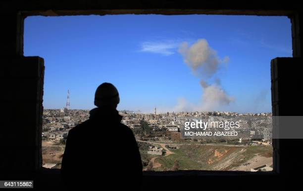 TOPSHOT A man looks at smoke billowing after a reported car bomb explosion at a Syrian progovernment position during clashes between rebel fighters...