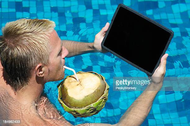 Man Looks at Tablet Computer Sipping Coconut in Pool