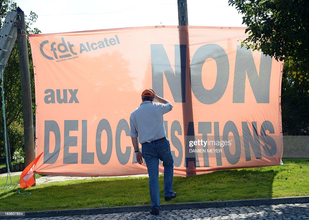 A man looks at the banner hung by French CFDT trade union reading : 'No to relocations' on October 8, 2013 in Orvault, western France, in front of a plant of French-US telecom-equipment maker Alcatel-Lucent, after the group announced the cut of 10,000 jobs worldwide to reduce fixed costs by 15 percent in two years, the company announced on October 8, 2013. The company said that 4,100 jobs would be cut in Europe, the Middle East and Africa by 2015, 3,800 in the Asia Pacific region, and 2,100 in North and South America.