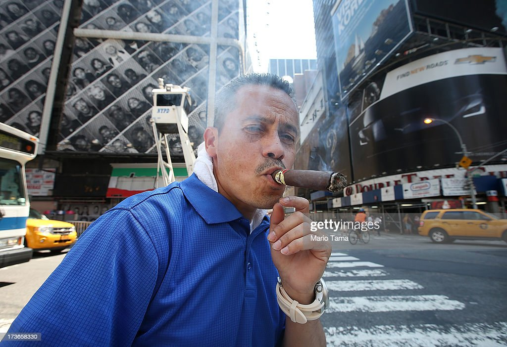 A man looks at the camera and smokes his cigar on his bicycle while stopped at a traffic light in the midday heat near Times Square on July 16, 2013 in New York City. The worst heat wave of the summer has descended on the city with temperatures in the mid-90's today.