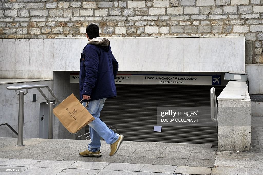 A man looks at the closed entrance to an Athens subway station, during a 24-hour employees strike to protest salary cuts as part of the new round of the austerity measures, on January 17, 2013. The employees annouced they will continue their protest the following days. The International Monetary Fund said Wednesday it would release 3.2 billion euros ($4.3 billion) in aid to Greece that had been frozen for months amid fears about the country's ability to surmount its debt crisis. AFP PHOTO/ Louisa Gouliamaki