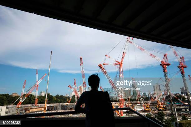 A man looks at the construction site for the National Stadium venue for the upcoming Tokyo 2020 Olympic Games in Tokyo on July 21 2017 The suicide of...