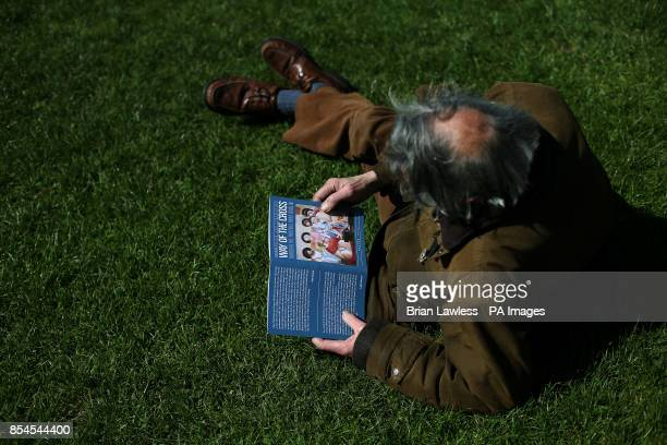 A man looks at the cover of the service booklet during the annual Good Friday 'Way of the Cross' procession from the Wellington Monument to the Papal...