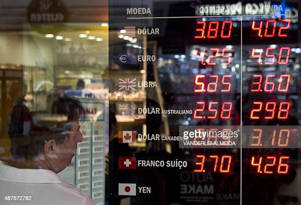 A man looks at the currencies board of a bureau de change in downtown Rio de Janeiro Brazil on September 10 2015 The Brazilian real devaluated...
