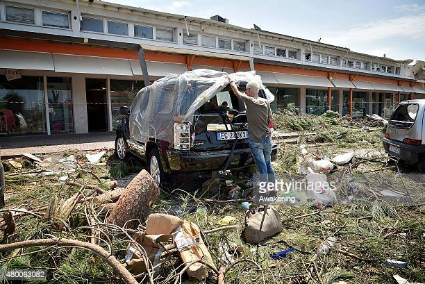 A man looks at the damage caused by last night tornado to his car on July 9 2015 in Venice Italy A tornado swept through the outskirts of Venice...