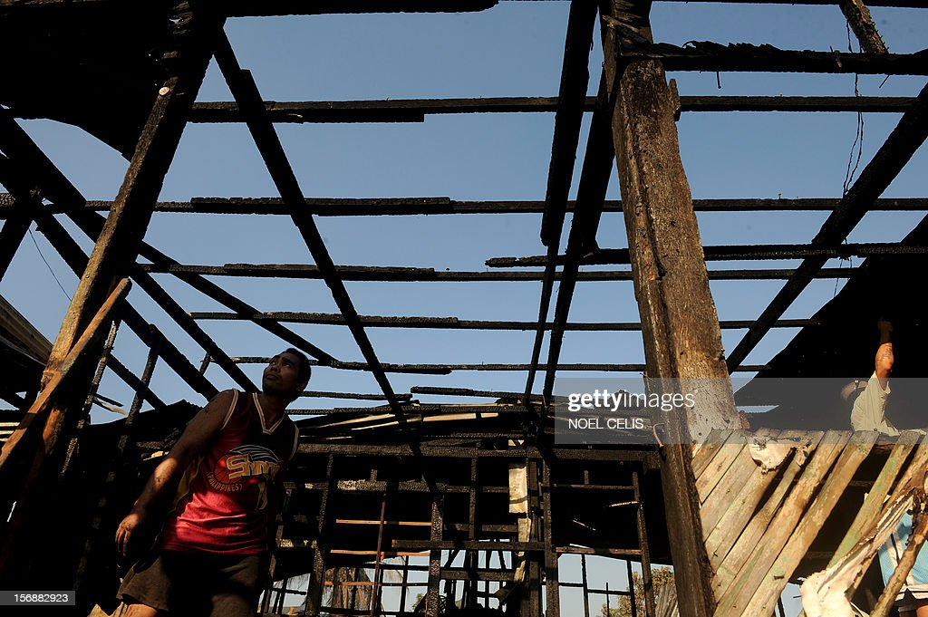 A man looks at the destroyed roof of his house in Manila on November 24, 2012 after an overnight fire razed a slum area. Three children died during the fire and almost 150 people were affected according to local media report.