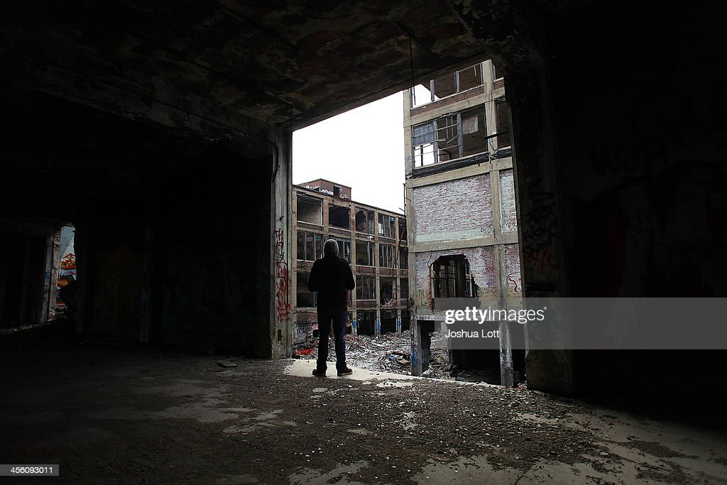 A man looks at the exterior of the abandoned Packard Automotive Plant December 13, 2013 in Detroit, Michigan. Peru-based developer Fernando Palazuelo made his final payment on the Packard Plant, which he won during a Wayne County auction for $405,000. Palazuelo plans on developing the former automotive plant where luxury Packard cars were made in the coming years.