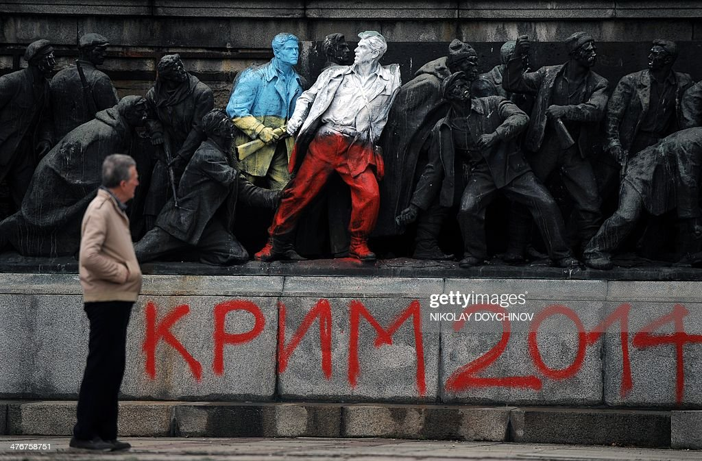 A man looks at the figures of Communist soldiers painted in the colours of the Ukranian and Polish flags by an unknown artist with the sign 'Crimea 2014' in central Sofia on March 5, 2014. The monument was painted overnight in Ukrainian and Polish national flag colours together with texts reading 'Crimea 2014' ,'Katyn 5.03.1940' and 'Putin go home!' The main Soviet army monument in Bulgaria's capital Sofia received a pro-Ukraine makeover a week ago as massive pro-European protests in the former Soviet country turned deadly in the past week.
