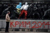 A man looks at the figures of Communist soldiers painted in the colours of the Ukranian and Polish flags by an unknown artist with the sign 'Crimea...