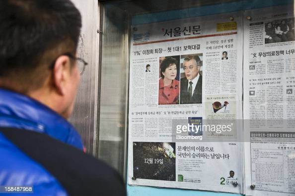 A man looks at the front page of a newspaper report on South Korean presidential candidates Park Geun Hye from the ruling New Frontier Party left and...