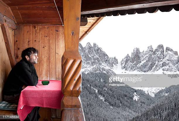 Man looks at the mountains from an alpine hut