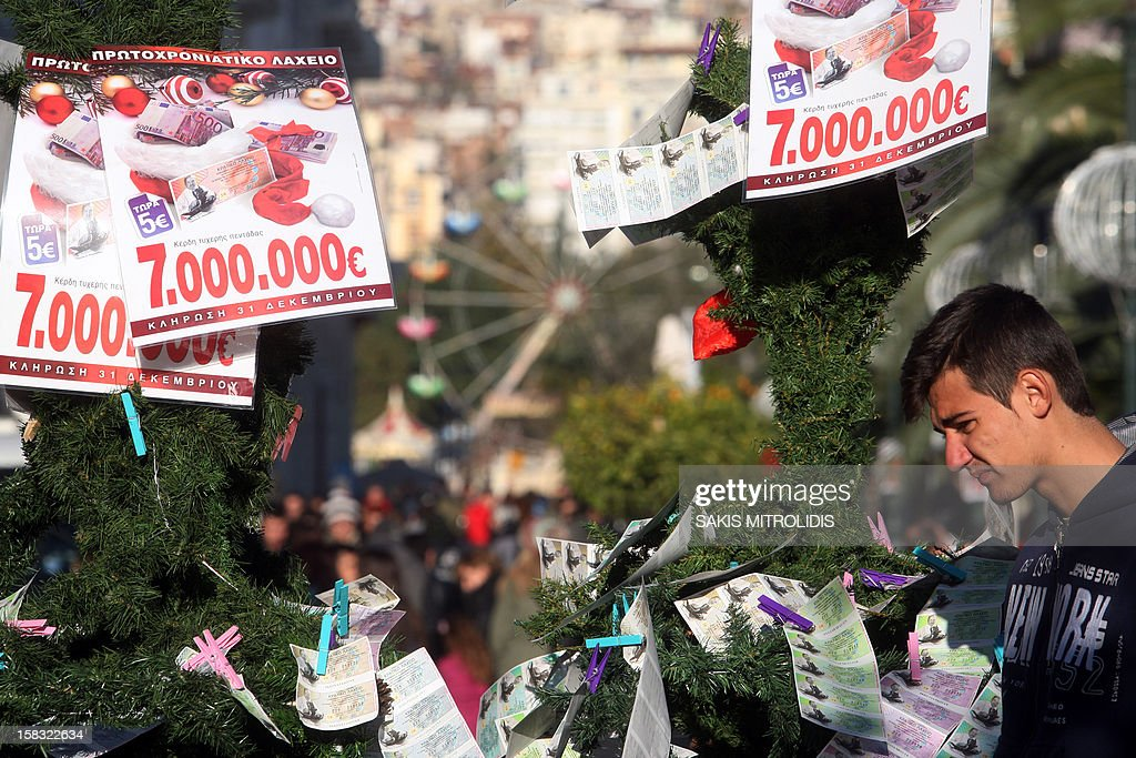 A man looks at the New Year's lottery tickets and ads hanging from a Christmas tree in Thessaloniki on December 13, 2012. Much-needed rescue funds for Athens 'will be flowing to Greece as early as next week,' the head of the Eurogroup Jean-Claude Juncker said on December 13. AFP PHOTO /Sakis Mitrolidis