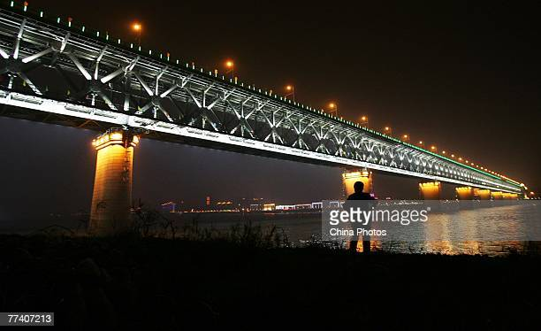 A man looks at the on the first Yangtze River Bridge as it is illuminated on October 18 2007 in Wuhan China Construction of the first Wuhan Yangtze...