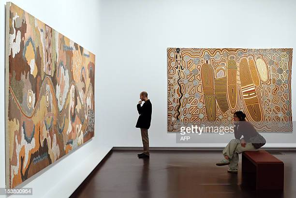 A man looks at the painting by Aborigine artist Clifford Possum Tjapaltjarri named 'Spirit dreaming through napperby country' on October 9 2012 at...