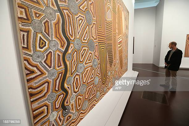 A man looks at the painting by Aborigine artist Uta Uta Tjangala name 'Old man's dreaming' on October 9 2012 at the Quai Branly museum for indigenous...