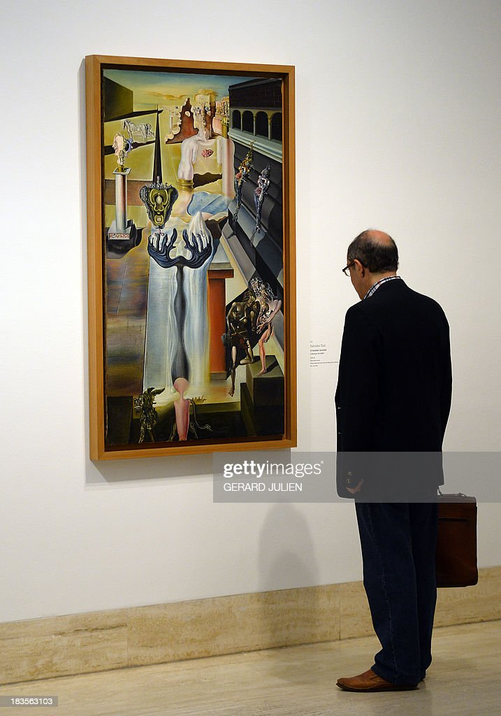 A man looks at the painting 'El hombre invisible' by Salvador Dali during the exhibition entitled 'Surrealism and the Dream' at the Thyssen-Bornemisza museum in Madrid, on October 7, 2013.