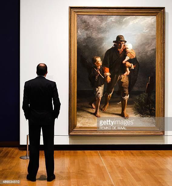 A man looks at the painting 'Langs Het Kerkhof/Langs Moeders Graf' by Dutch painter Jozef Israels during a press preview of the exhibition 'Munch Van...