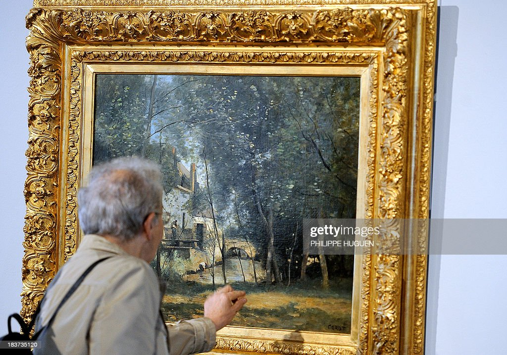 LAOUCHEZ A man looks at the painting 'Le Moulin de Saint-Lez-Arras' by French painter Camille Corot during the exhibition 'Corot in the light of the North' on October 7, 2013 at the La Chartreuse museum in Douai, northern France. The event is held from October 5, 2013 to January 6, 2014. AFP PHOTO PHILIPPE HUGUEN