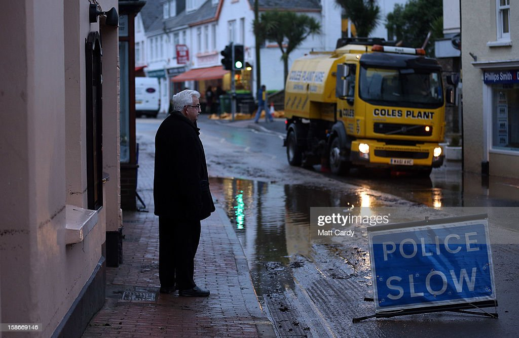 A man looks at the receding flood water and the clean up operation taking place in the centre of the Devonshire town of Braunton that was flooded yesterday on December 23, 2012 near Barnstaple, England. Flooding has brought further disruption to many parts of the UK including the South West of England that was particularly badly hit. The Met Office are warning of further bands of heavy rain tonight and the Environment Agency has issued 100s of flood warnings for England including one severe warning for Cornwall.