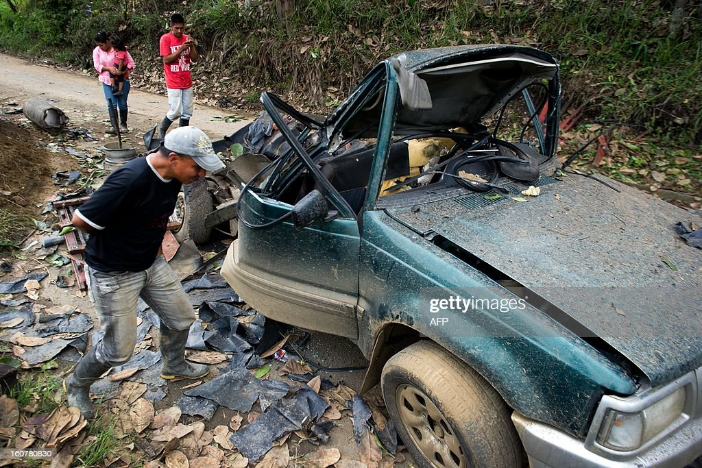 A man looks at the remains of a car bomb in El Palo, department of Cauca, Colombia, on February 5, 2013. Two car bombs were detonated allegedly by Revolutionary Armed Forces of Colombia (FARC) guerrillas at a military checkpoint in southwestern Colombia Tuesday, killing a civilian and a soldier, and injuring three soldiers. AFP PHOTO/LUIS ROBAYO