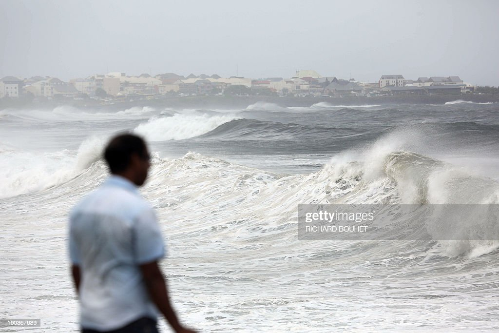 A man looks at the sea on the North coast of French Indian Ocean island of La Reunion on January 30, 2013 near Saint-Denis, as high waves hit the coastline. The cyclone Felleng was announced at 735 Km north of the island and progresses at the speed of 17 Km per hour. Felleng should approach the coast of the island from 300 km on February 1st. AFP PHOTO RICHARD BOUHET