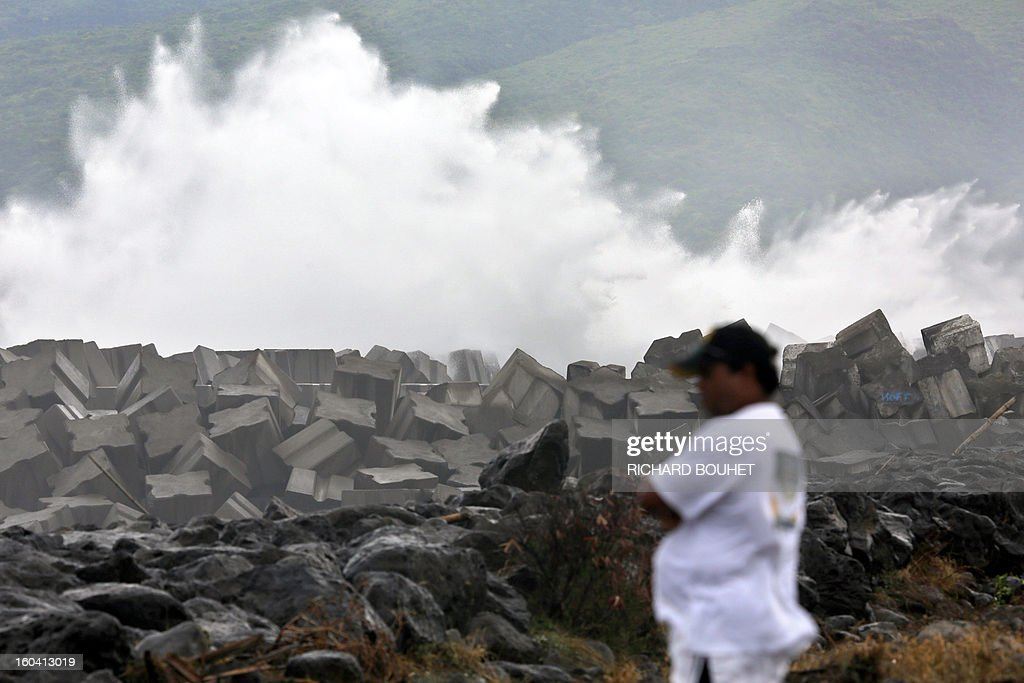 A man looks at the sea on the northwestern coast of French Indian Ocean island of La Reunion on January 31, 2013 near Saint-Paul, as high waves hit the coastline, caused by the cyclone Felleng at 530 Km north of the island. BOUHET