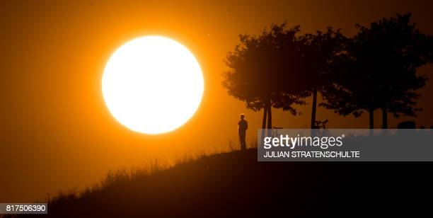 TOPSHOT A man looks at the setting sun on July 17 2017 near Hanover northern Germany / AFP PHOTO / dpa / Julian Stratenschulte / Germany OUT