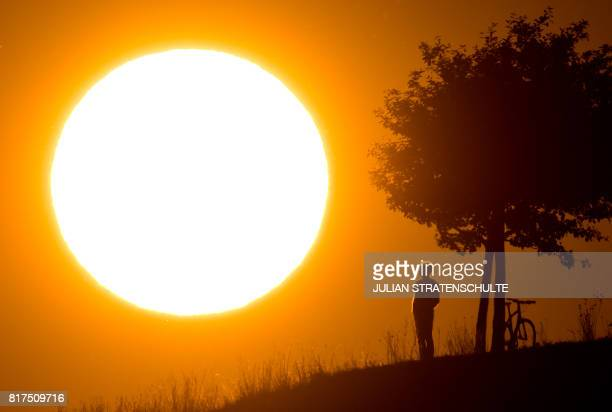 A man looks at the setting sun on July 17 2017 near Hanover northern Germany / AFP PHOTO / dpa / Julian Stratenschulte / Germany OUT