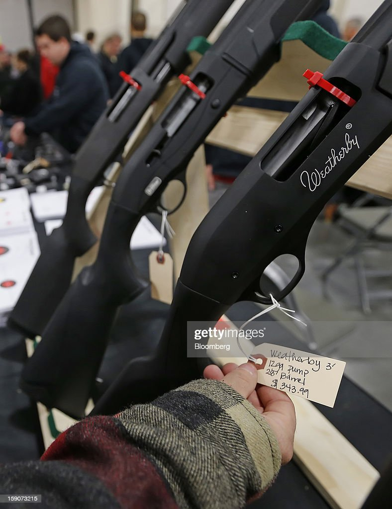 A man looks at the tag of a Weatherly shot gun for sale at the Rocky Mountain Gun Show in Sandy, Utah, U.S., on Saturday, Jan. 5, 2013. A working group led by Vice President Joe Biden is seriously considering measures that would require universal background checks for firearm buyers, track the movement and sale of weapons through a national database, strengthen mental health checks and stiffen penalties for carrying guns near schools or giving them to minors. Photographer: George Frey/Bloomberg via Getty Images