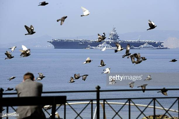 A man looks at the USS Enterprise the first nuclearpowered aircraft carrier in Athens on March 29 2012 The 342meter ship which is the longest naval...