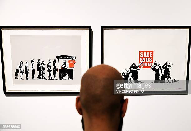 A man looks at the works entitled 'Festival' and 'Sale Ends' made by Englandbased graffiti artist Banksy during the 'Guerra Capitalismo Liberta '...
