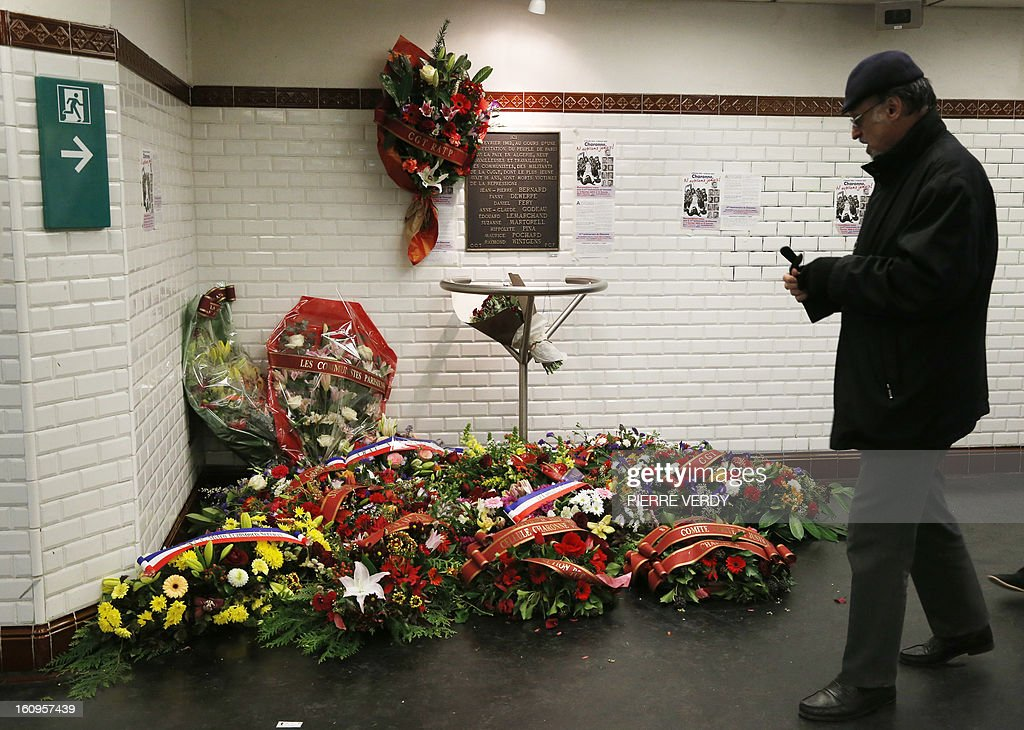 A man looks at the wreaths placed below a commemorative plaque, inside Charonne underground metro, on February 8, 2013 in Paris during a commemoration ceremony to mark the 51th anniversary of the February 8, 1962 killing by police of nine demonstrators at the Paris Charonne metro station during a peaceful, but outlawed demonstration which had seen some 30,000 people rally to call for peace in Algeria.
