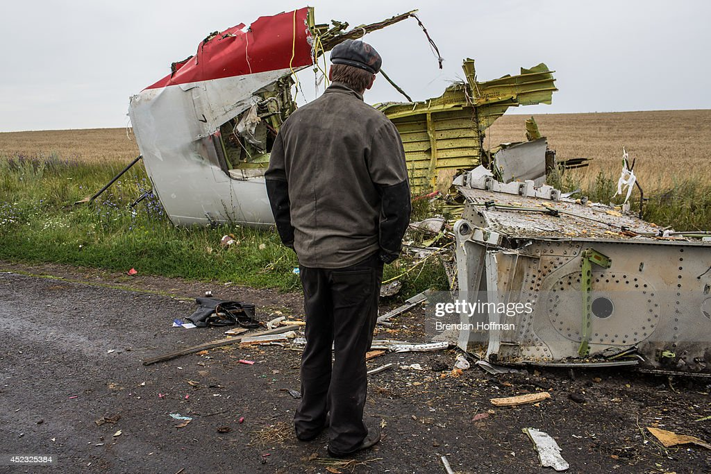 A man looks at the wreckage of passenger plane Malaysia Airlines flight MH17 on July 18, 2014 in Grabovka, Ukraine. Malaysia Airlines flight MH17 travelling from Amsterdam to Kuala Lumpur crashed yesterday on the Ukraine/Russia border near the town of Shaktersk. The Boeing 777 was carrying 298 people including crew members, the majority of the passengers being Dutch nationals, believed to be at least 173, 44 Malaysians, 27 Australians, 12 Indonesians and 9 Britons. It has been speculated that the passenger aircraft was shot down by a surface to air missile by warring factions in the region.
