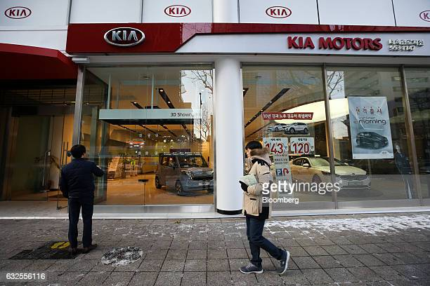 A man looks at vehicle specifications presented in a 3D hologram that is projected onto a window at a Kia Motors Corp dealership in Seoul South Korea...