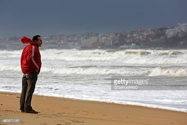A man looks at waves at Somo beach near Santander on January 31 2015 Fierce waves were pounding seafronts and fishing boats off northern Spain where...