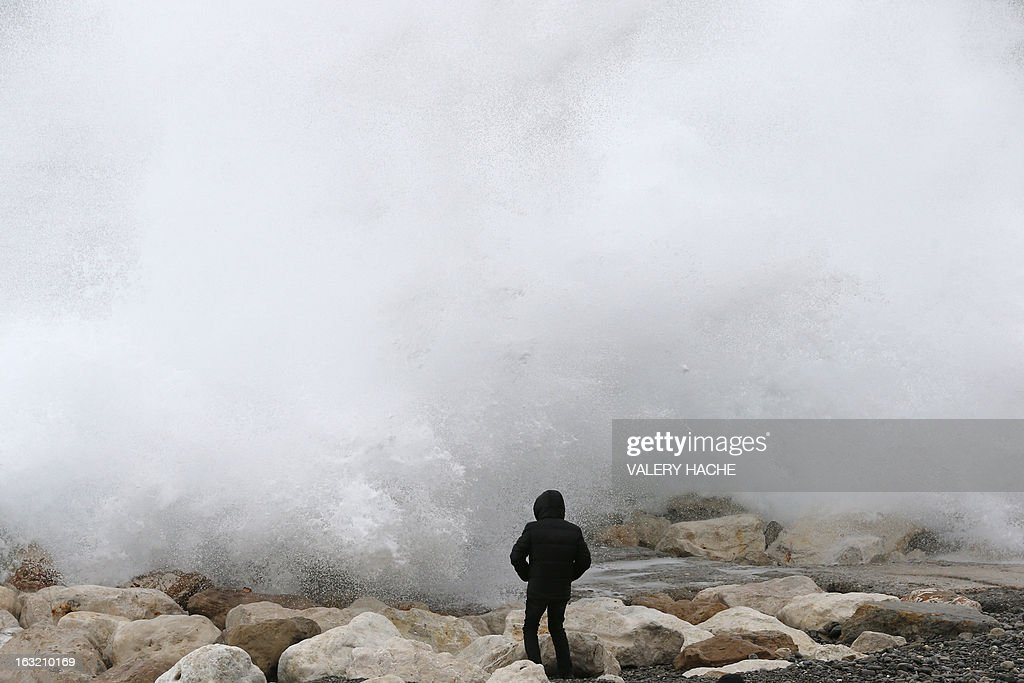 A man looks at waves breaking on the rocks on the beach along the 'Promenade des Anglais', on March 6, 2013 in Nice, southeastern France. AFP PHOTO / VALERY HACHE
