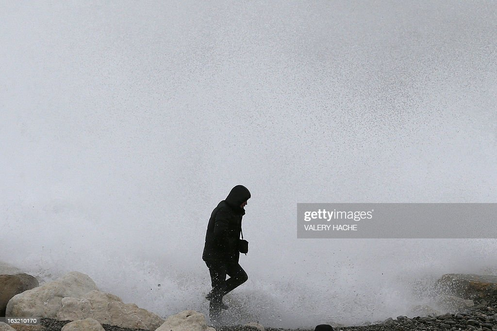 A man looks at waves breaking on the rocks on the beach along the 'Promenade des Anglais', on March 6, 2013 in Nice, southeastern France.