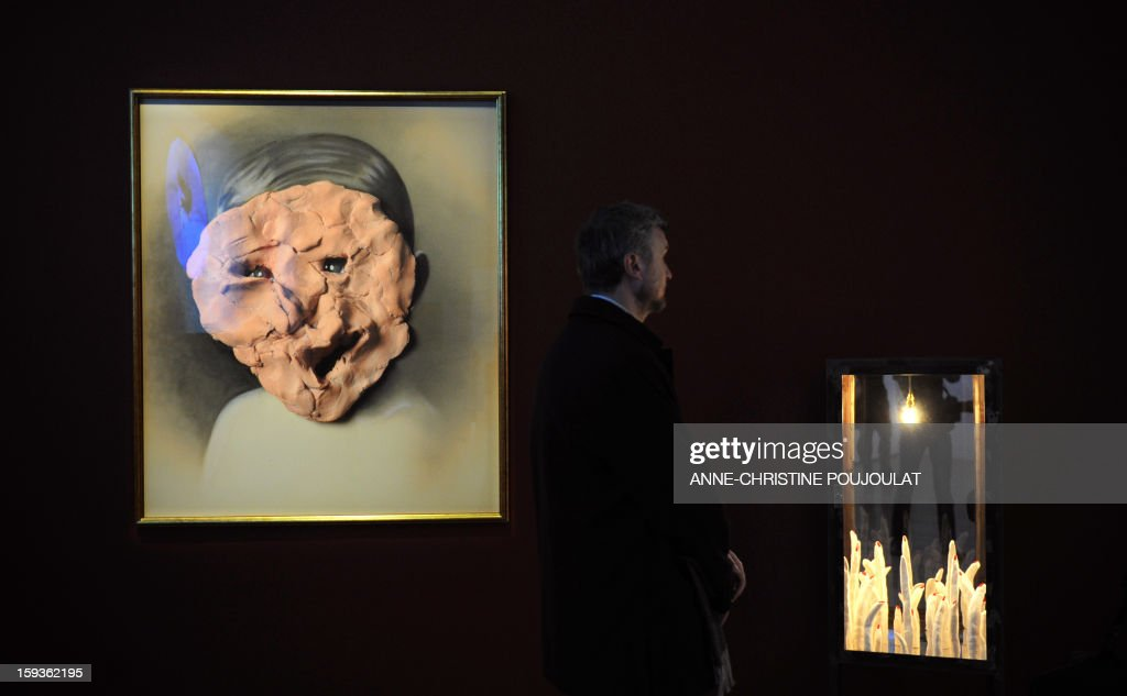 A man looks at works of Spanish artist Carmen Calvo 'El Rostro' (L) and 'Quand s'ouvrent lentement tes grandes portes noires' (R), displayed at the Granet museum on January 11, 2013, in Aix-en-Provence, at the 'Exquisite corpse, mediterranean suite' exhibition, one of the events marking the beginning and launch of festivities for the Marseille-Provence 2013 European Capital of Culture.