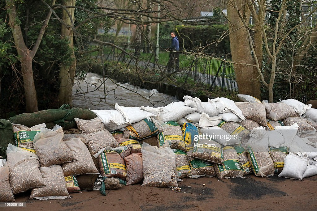 A man looks back at some of the hastily made flood defences in the centre of the Devonshire town of Braunton that was flooded yesterday on December 23, 2012 near Barnstaple, England. Flooding has brought further disruption to many parts of the UK including the South West of England that was particularly badly hit. The Met Office are warning of further bands of heavy rain tonight and the Environment Agency has issued 100s of flood warnings for England including one severe warning for Cornwall.
